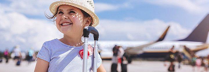 Menina segurando a mala de viagem