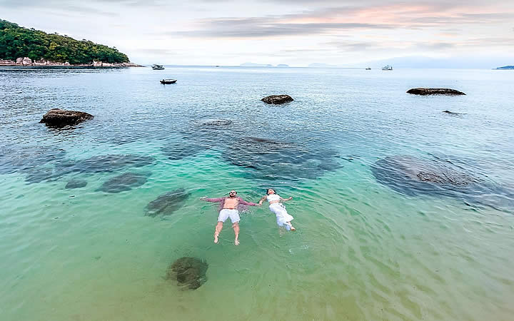 Casal nadando na praia da Ilha das Couves