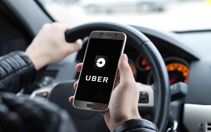 Homem segurando telefone com o app do Uber