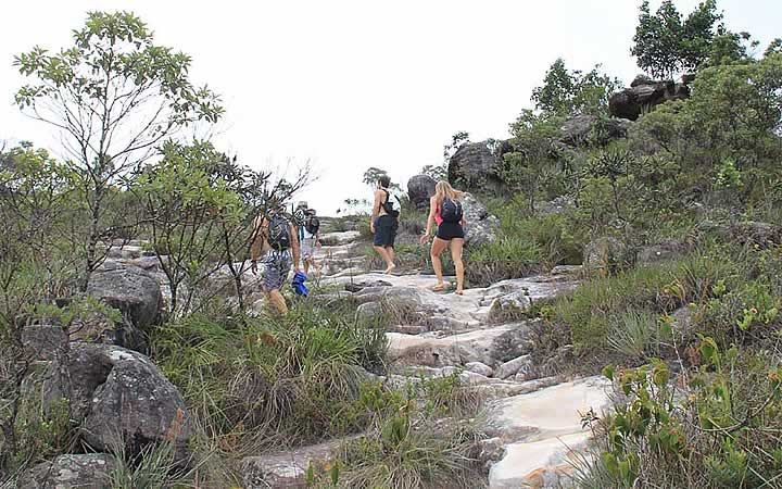 Pessoas fazendo trilha para chegar na Cachoeira da Fumaça
