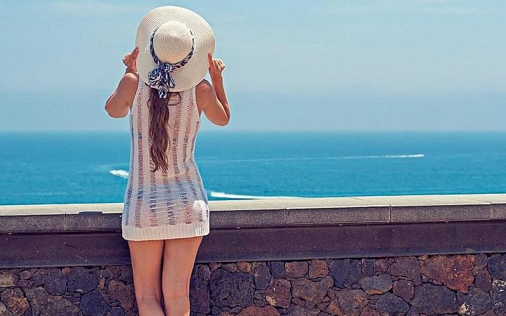 Mulher com chapéu olhando mar - O Que Levar Para Praia