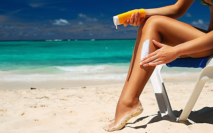 Pessoa passando protetor solar na perna
