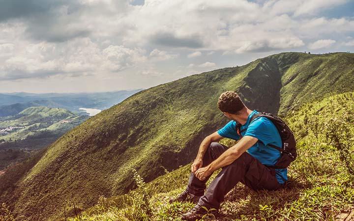 Homem sentado no alto da montanha - Viajar Sozinho