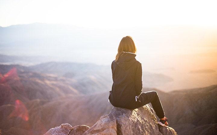 Menina sentada olhando mirante - Viajar sozinho