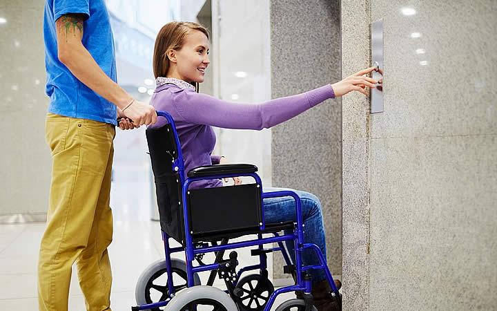 Mulher apertando o botão do elevador