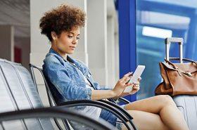 Mulher sentada olhando no celular - Dica útil para viajantes de ônibus