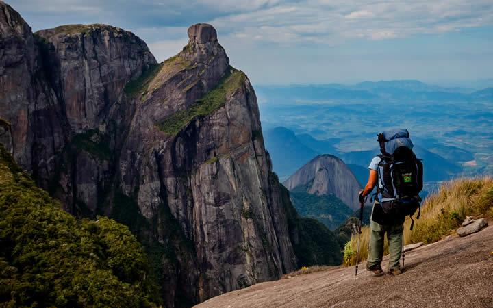 Pessoa em cima de uma pedra apreciando a vista - Parque Nacional da Serra dos Órgãos