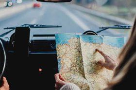 Pessoas dentro do carro com mapa de viagem